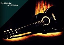 Una guitarra acústica negra puesta sobre el suelo