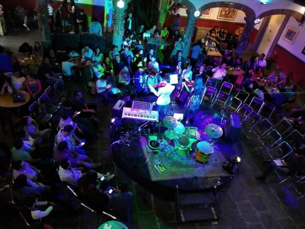 Gente en un concierto admirando y aplaudiendo a unos de violinistas